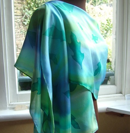 The silk scarf draped and pinned on one shoulder